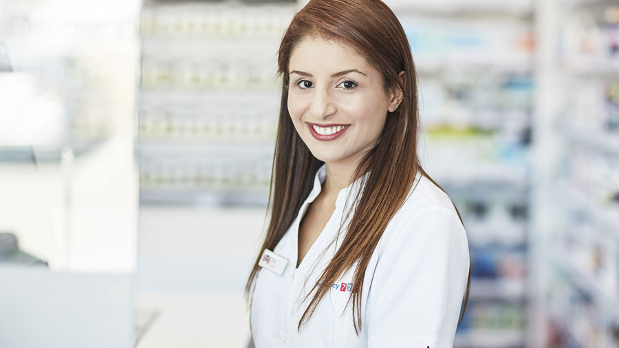 Pharmacist behind the counter in a Pharmacy 777 uniform